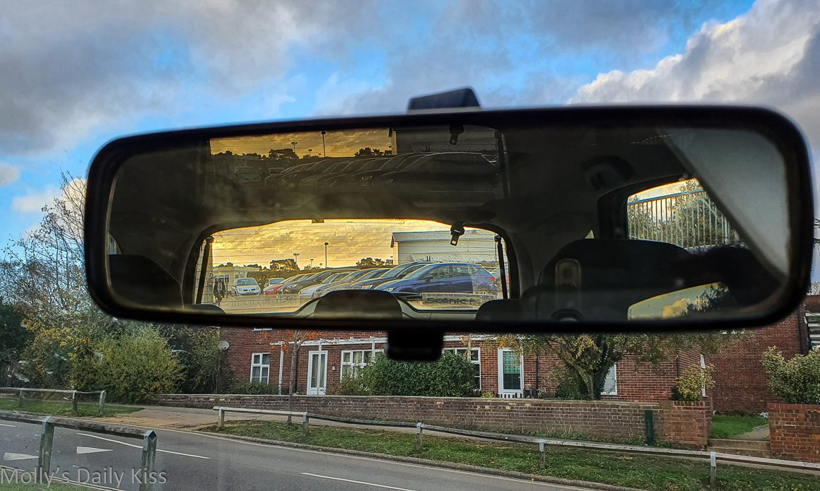 sunset in rearview mirror at the end of the day