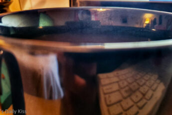 Coffee cup with desk reflected in the edge