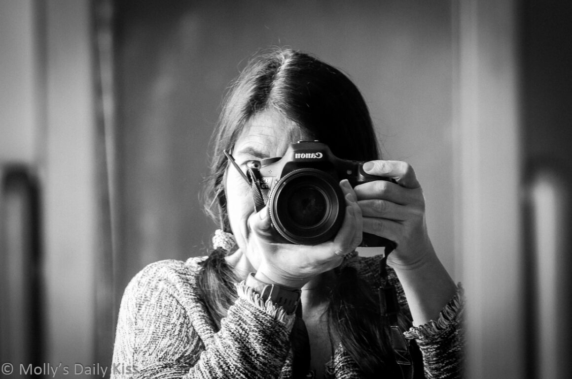 self portrait in the mirror with camera in black and white