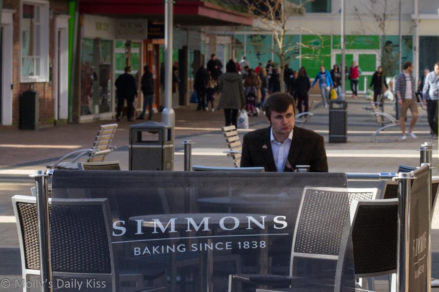 man eating at street cafe alone people watching