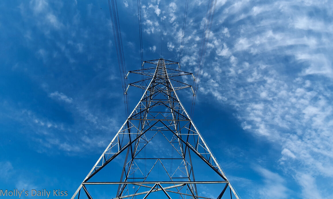 Looking up at electricity pylon against blue sky with wispy white clouds
