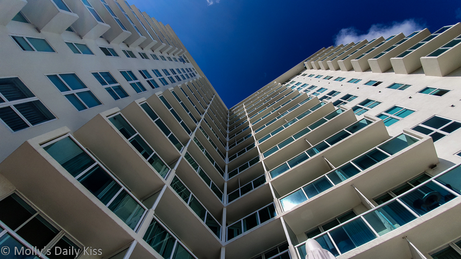 Looking up at lofty white tall building to blue sky above