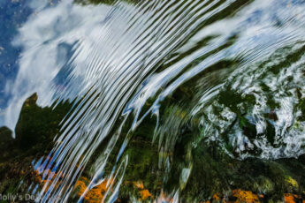 Sky reflected in water next to ripples over a rock