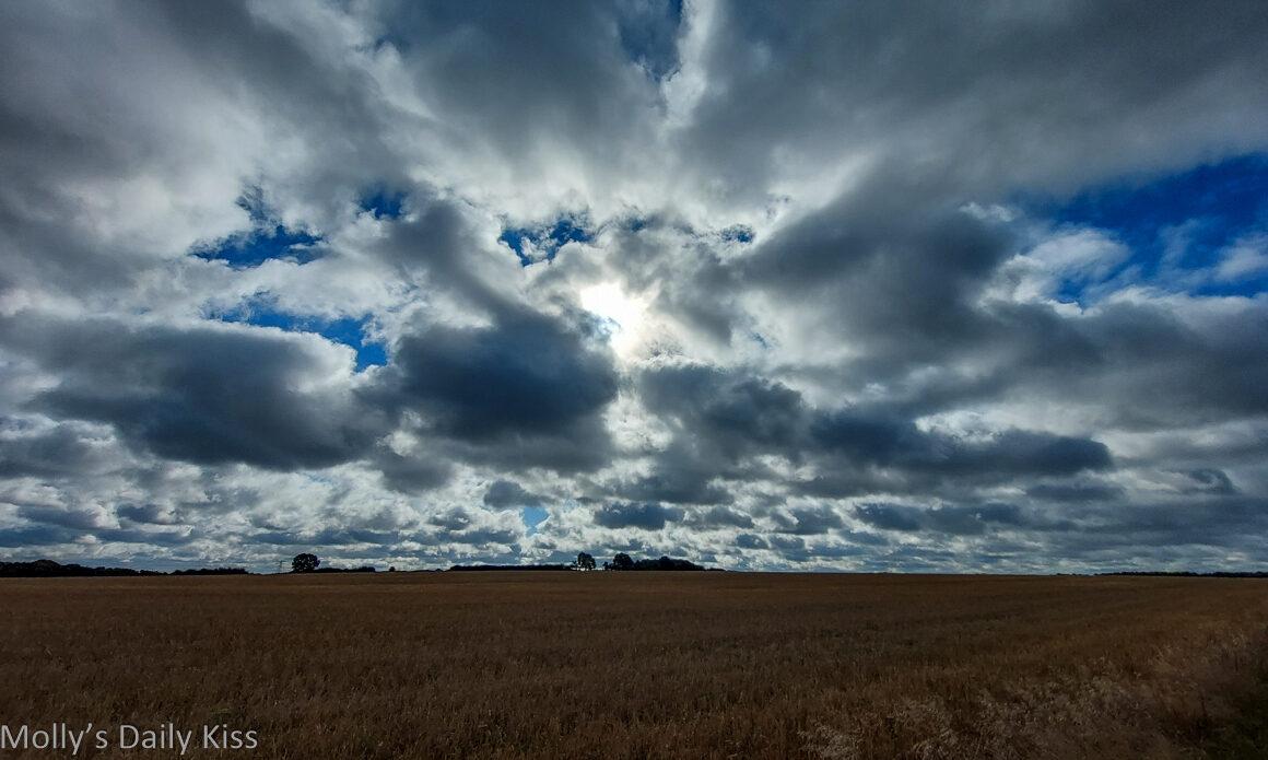 Sun shining through broken clouds over fields